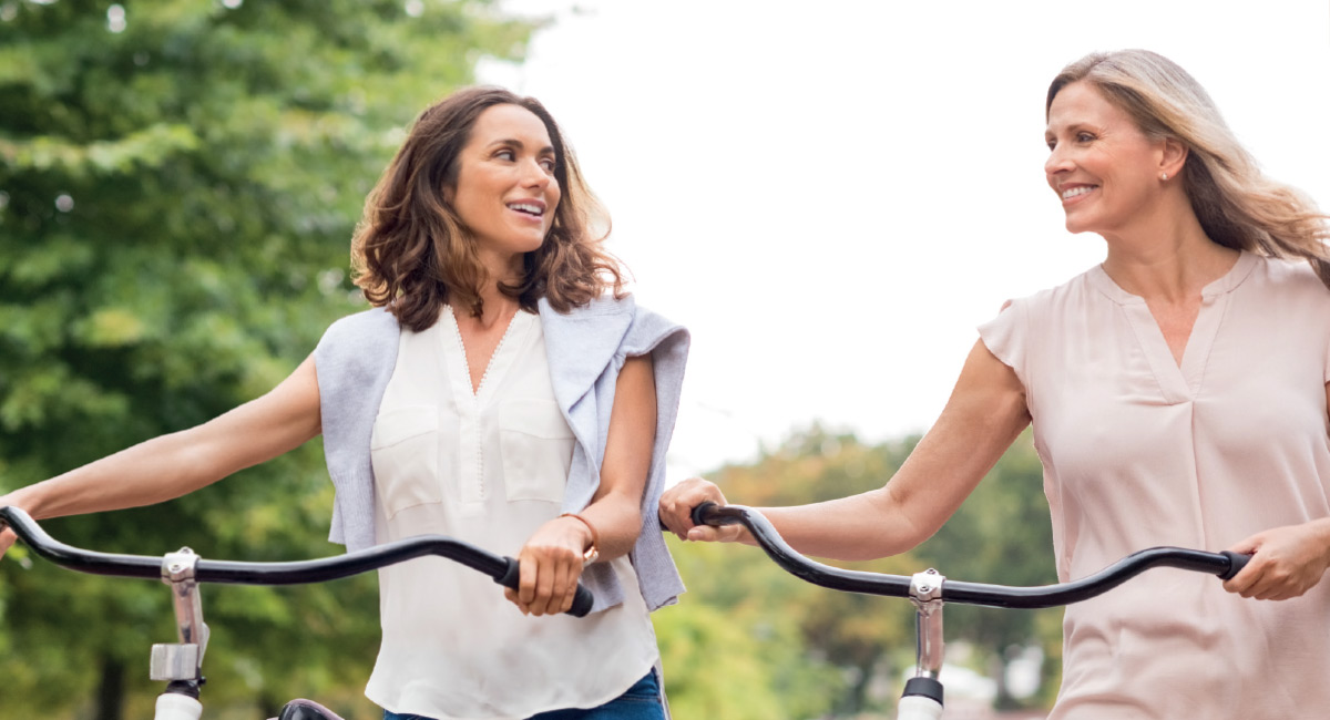 Women Walking With Bicycles