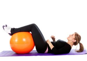 Girl on an excercise matt with a swiss ball
