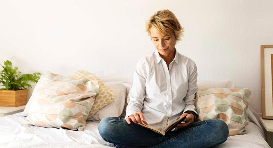 Woman Sitting Cross Legged on Bed Reading Book
