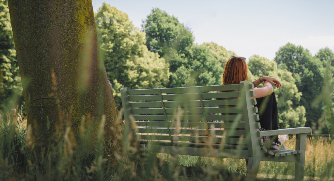 Woman Sitting Up on Park Bench by Tree