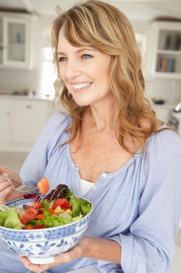 Mid age woman eating salad