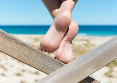 Womans bare feet on wood at beach